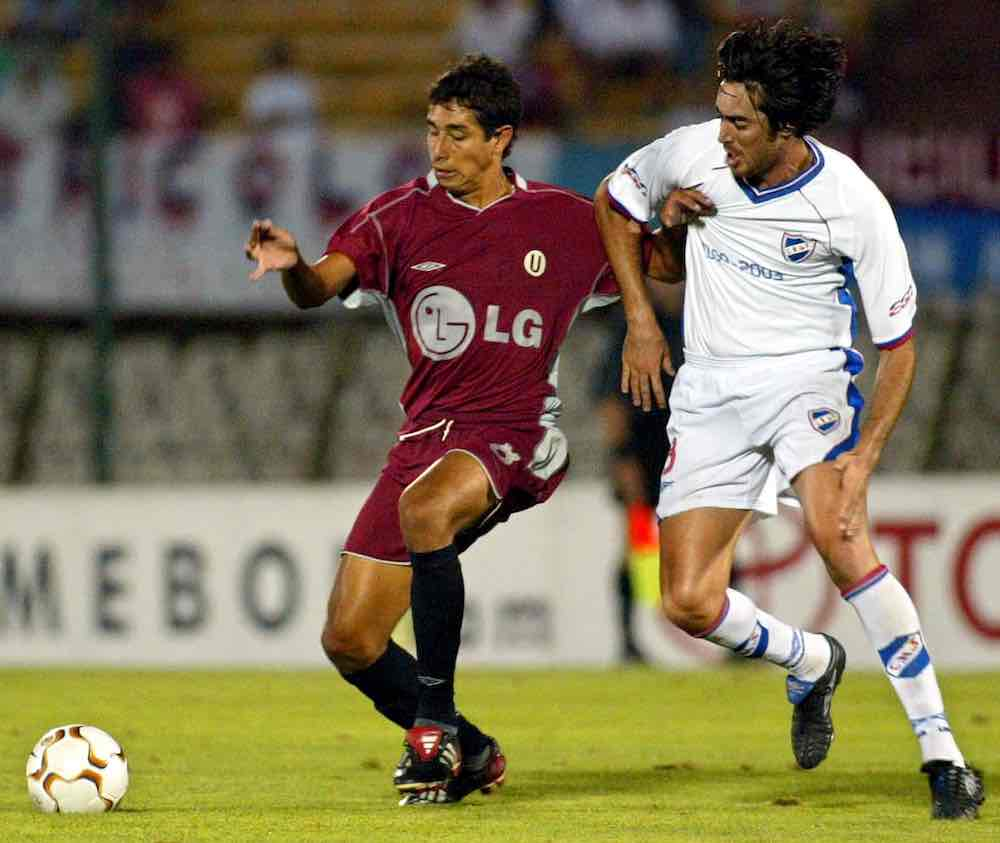Juan Cominges of Universitario of Lima is challenged by Marco Vanzini of Nacional